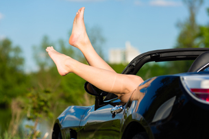 young woman or legs in a convertibleの写真素材 [FYI00868010]