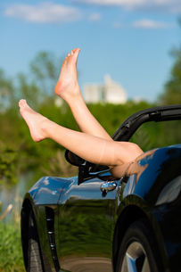 young woman lets her legs in the summer hanging out of a convertibleの写真素材 [FYI00868019]