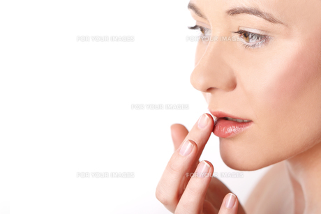 young woman putting cream on her lips aの写真素材 [FYI00868086]