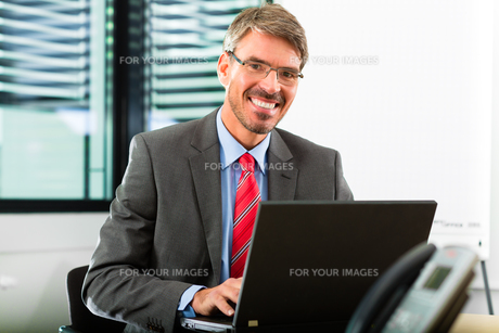 businessman with laptop in his officeの写真素材 [FYI00868777]