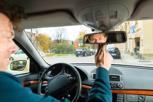 a taxi driver looks in the rear view mirrorの素材 [FYI00868845]