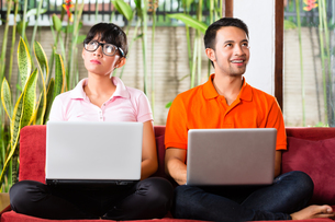 asian couple on the couch with a laptopの写真素材 [FYI00868860]