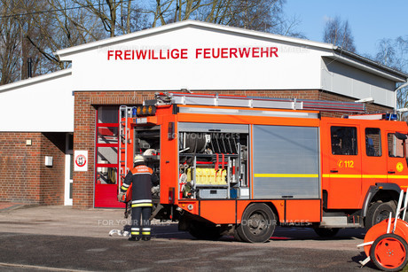 firefighter on fire truck in front of the fire stationの写真素材 [FYI00869066]