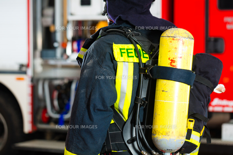 firefighter standing in uniform in front of a fireの写真素材 [FYI00870012]
