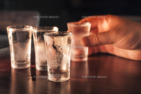 shot glasses of vodka on a wooden table,addiction to alcohol.の写真素材 [FYI00872155]
