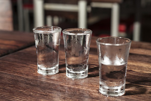 shot glasses of vodka on a wooden table,addiction to alcohol.の写真素材 [FYI00872170]