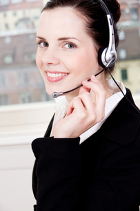 young brunette woman working in a call center with headsetの写真素材 [FYI00873395]