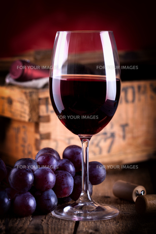 glass of red wine before old wine crateの写真素材 [FYI00873749]