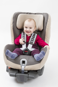 happy child in booster seat for a car in light backgroundの写真素材 [FYI00875101]