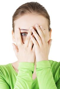 shy or scared teenage girl peeking through covered faceの写真素材 [FYI00875786]