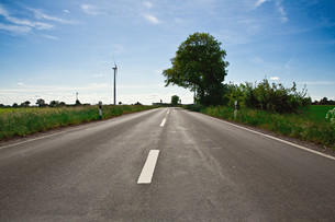 empty road with blue sky and wind turbinesの写真素材 [FYI00876558]