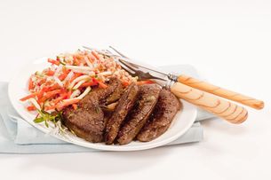 fried liver on a plate served with spelled-carrot saladの写真素材 [FYI00877783]