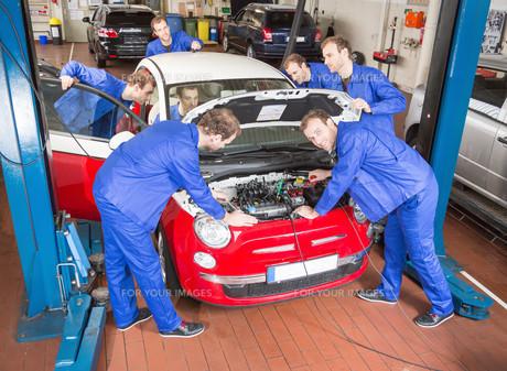 car mechanic in workshop for the repair of a carの写真素材 [FYI00879413]