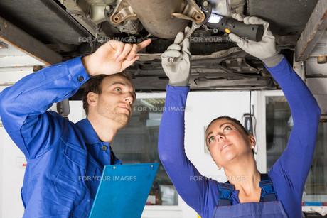 two mechanics repairing a carの写真素材 [FYI00879417]