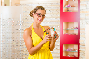 young woman at the opticians buys glassesの素材 [FYI00879875]