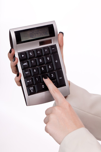 young businesswoman smiling with calculator isolatedの写真素材 [FYI00879887]