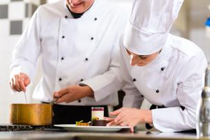 team of chefs with dessert in kitchenの写真素材 [FYI00879888]