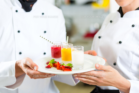 team of chefs with dessert in kitchenの写真素材 [FYI00879925]