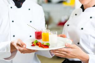 team of chefs with dessert in kitchenの写真素材 [FYI00879925]