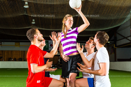 woman has a soccer ball in hand,men kneelの写真素材 [FYI00879939]