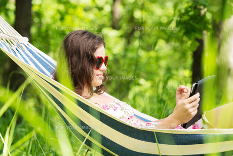 young woman lying in a hammock in the garden with e-book.の写真素材 [FYI00879980]