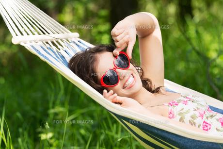 young woman lying in a hammockの写真素材 [FYI00880052]