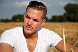 portrait of a beautiful young man outdoors in white casual shirt sitting on hay fieldの写真素材 [FYI00881225]