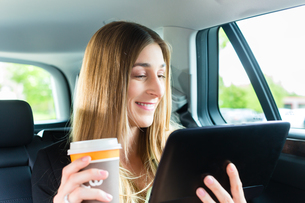 woman travels in taxi with coffee and tablet computersの素材 [FYI00882016]