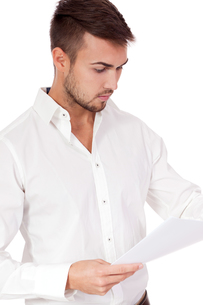 young adult businessman reading a document isolatedの写真素材 [FYI00882250]