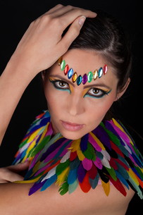 beautiful young woman with colorful feather headdress and makeupの写真素材 [FYI00883150]