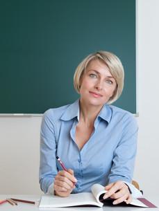 teacher sitting at desk in classroomの写真素材 [FYI00883237]