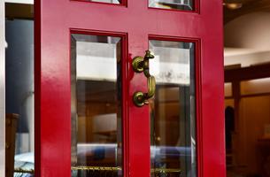 部屋の入口の赤いドアと金属の取っ手の写真素材 [FYI00887176]