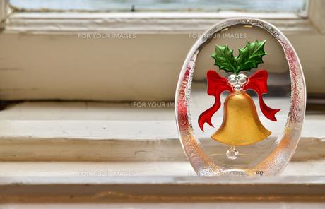 窓のそばに置かれた鐘の模様のガラスの置物の写真素材 [FYI00887661]