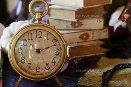 部屋のテーブルの上の古い置時計と本の写真素材 [FYI00888782]