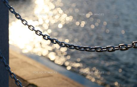 夕暮れの港の岸辺の柵の鎖の写真素材 [FYI00889182]