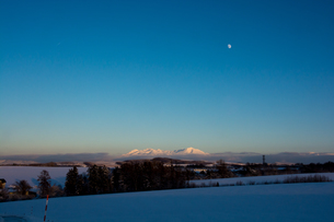 夕暮れの雪山と十三夜の月の写真素材 [FYI00890345]