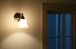 部屋の壁の灯りと窓の夜景の写真素材 [FYI00890724]