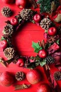 赤い林檎のクリスマスリースとクリスマスツリー 赤色背景の写真素材 [FYI00892421]