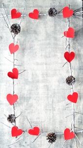 赤いハート型の切り絵と松ぼっくり フレームの写真素材 [FYI00892451]