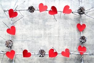 赤いハート型の切り絵と松ぼっくり フレームの写真素材 [FYI00892452]
