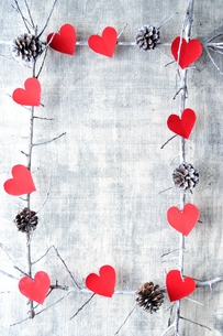 赤いハート型の切り絵と松ぼっくり フレームの写真素材 [FYI00892453]