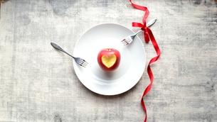 ハート型に皮をくりぬいた林檎と2本のフォークの写真素材 [FYI00892536]