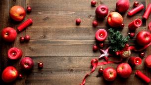 ミニクリスマスツリーと林檎と赤いキャンドル 木材背景の写真素材 [FYI00892605]