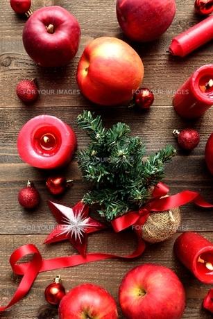 ミニクリスマスツリーと林檎と赤いキャンドル 木材背景の写真素材 [FYI00892606]