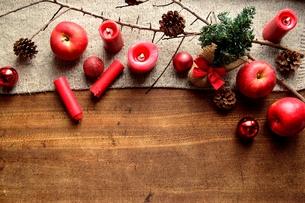 ミニクリスマスツリーと林檎と赤いキャンドル ニット生地背景の写真素材 [FYI00892611]