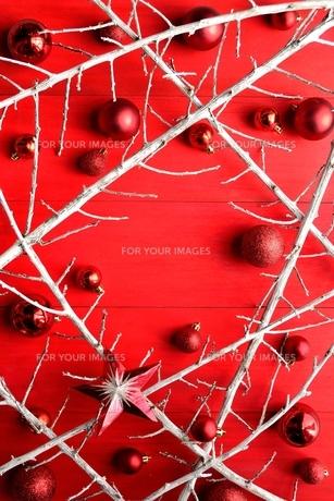 白い枯枝と赤いクリスマスオーナメント 赤木材背景の写真素材 [FYI00892635]