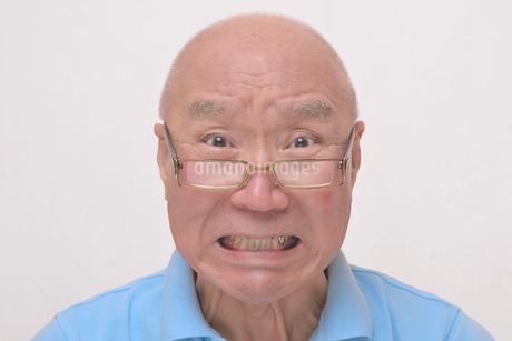 老眼鏡をかけた怒り顔のシニアの写真素材 [FYI00892861]