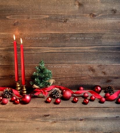 赤いクリスマス飾りとキャンドルとクリスマスツリーの写真素材 [FYI00893203]