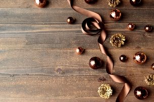 ブラウンのクリスマスオーナメントとリボン 黒木材背景の写真素材 [FYI00893221]