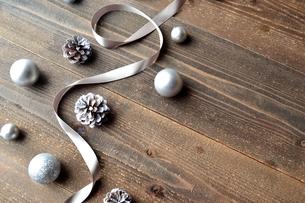 銀色のクリスマスオーナメントとリボン 黒木材背景の写真素材 [FYI00893223]